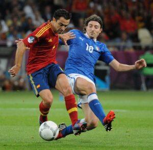 Xavi (links) draait zich af van Riccardo Montolivo (Italië) in de finale van Euro 2012