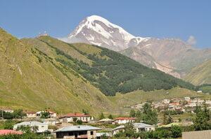 De Kazbek, het dorp Gergeti en boven het dorp de Drievuldigheidskerk van Gergeti
